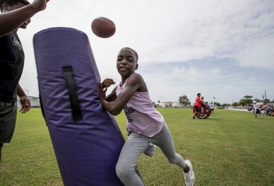 De'Vondre Campbell, Cypress Lake grad and Atlanta Falcons linebacker held a youth football camp for boys and girls 8-17. Dariona Gary 10, hits the bag as she runs drills.
