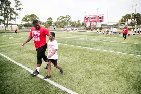 """We'll get you some food,"" Immokalee High School graduate and NFL player Deadrin Senat tells a camper on Saturday at the Rising Stars football camp at Immokalee High School. The camper said he had not eaten before coming to camp. Senat joined fellow graduates and NFL players Mackensie Alexander, D'Ernest Johnson and J.C. Jackson in leading the camp — which was presented by the Tommy Bohanon Foundation."