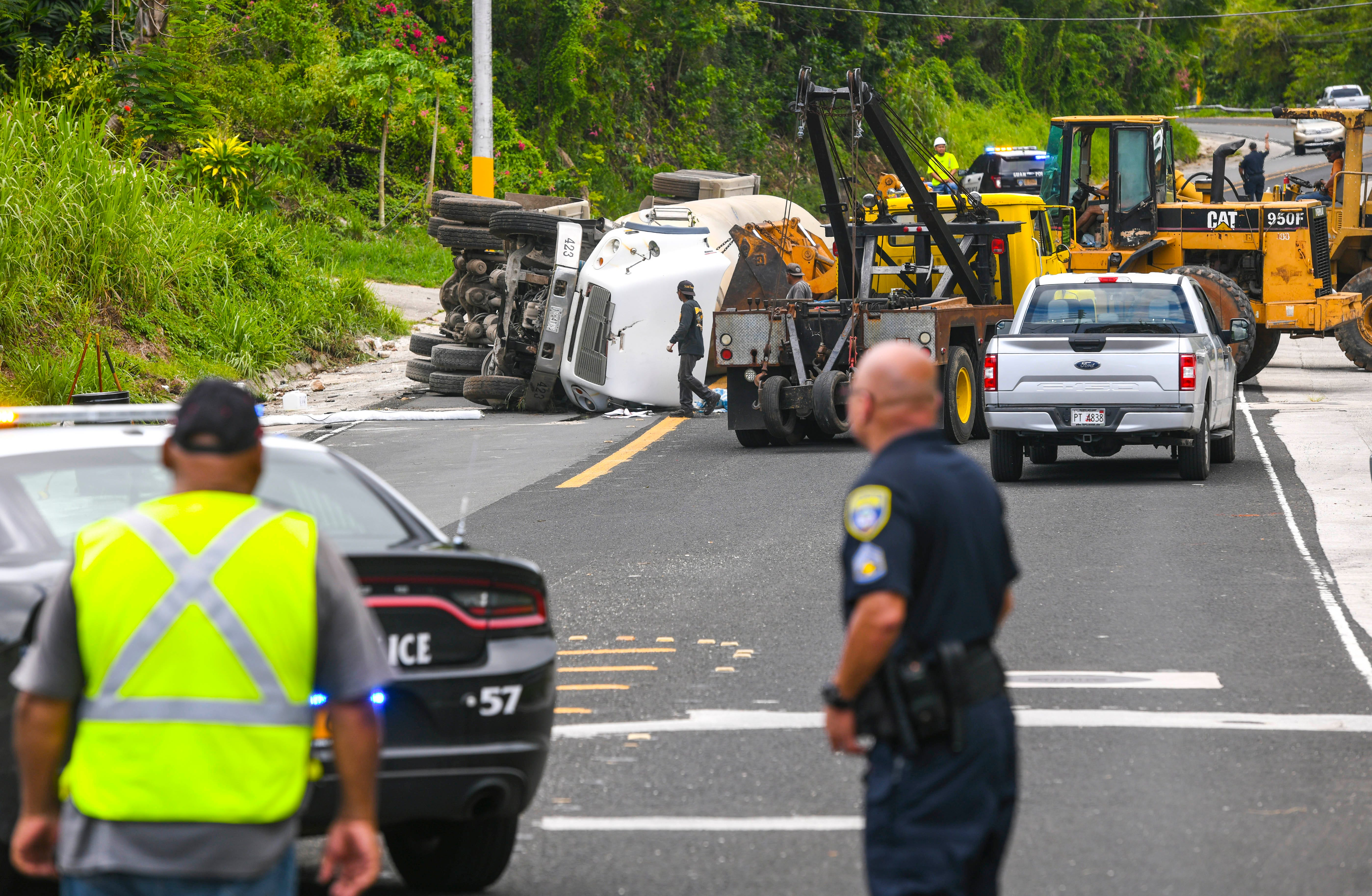 Guam Police Department officers redirect traffic on Route 6 as Department of Public Works employees and other emergency personnel respond to the crash of a tractor hauling a bulk cement transporter, near the Pacific War Museum, on Saturday, July 12, 2019.