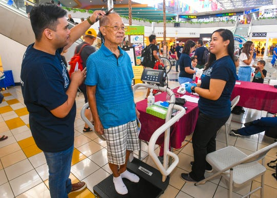 Dededo resident Alfredo Manapat gets his height recorded, by Registered Nurse Arnel Zantua, as part of his vital statistics during the Guam Regional Medical City's third annual Health Fair, held at the Micronesia Mall on Saturday, July 13, 2019.