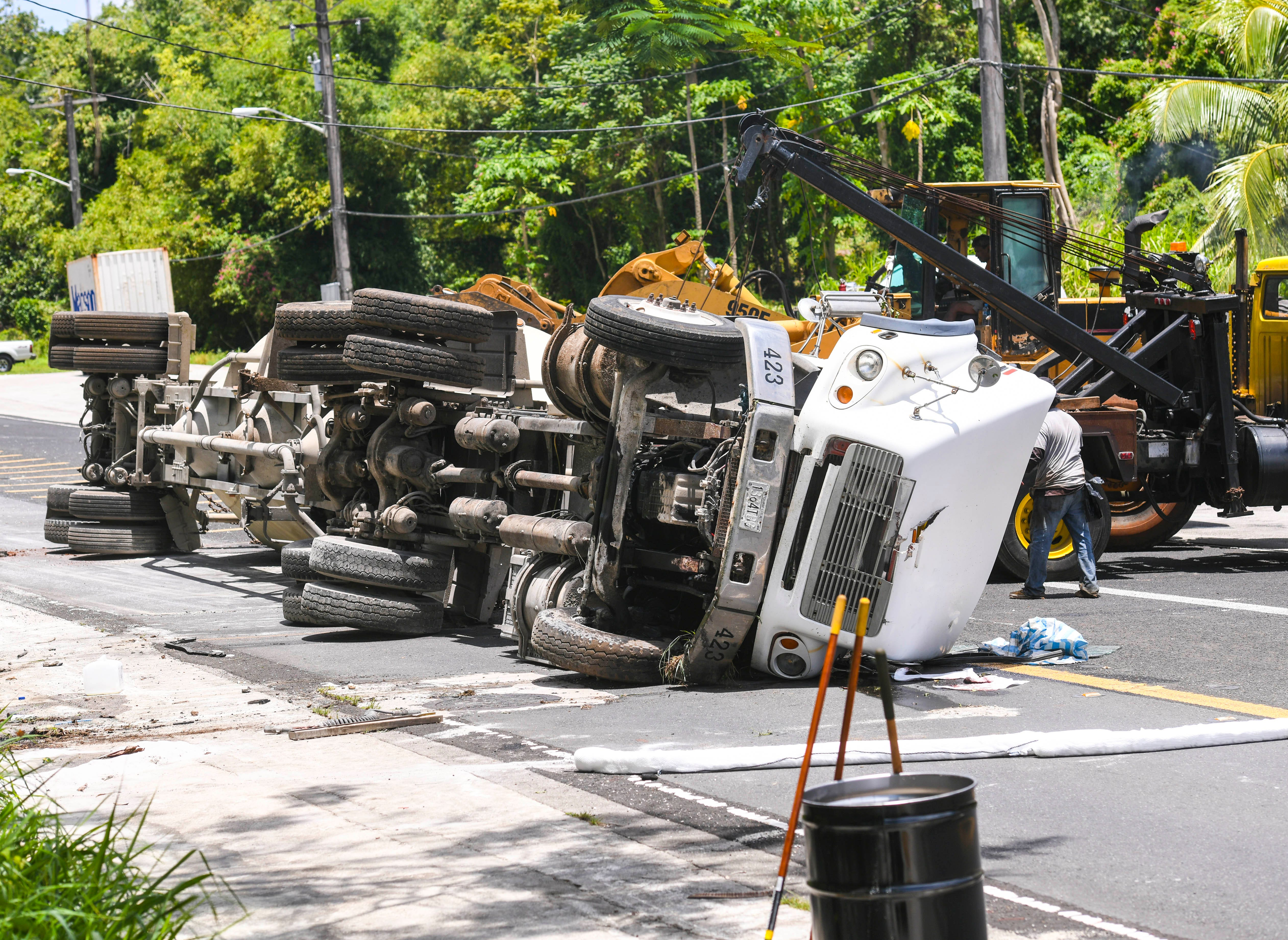 Department of Public Works employees and other emergency personnel respond to the crash of a tractor hauling a bulk cement transporter, on Route 6 near the Pacific War Museum, on Saturday, July 12, 2019.