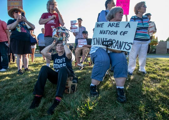 Nancy Kohn, left, and Ellen Haury, sit in the lawn during Lights for Liberty Vigil to end human detention camps, Friday, July 12, 2019, at 5652 W. 73rd St., Indianapolis.