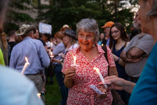 "Polly Murphy of Knoxville participates in candle lighting during the Lights for Liberty rally at Krutch Park in downtown Knoxville Friday, July 12, 2019. The rally took place to support immigrants, families being separated at the border and to inform the community about the 287(g) program, an agreement to voluntarily detain immigrants for Immigration and Customs Enforcement, implemented by former Sheriff Jimmy ""J.J."" Jones."