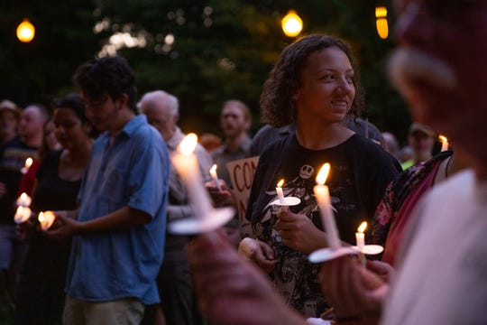 "Rally goers light their candles during the Lights for Liberty rally at Krutch Park in downtown Knoxville Friday, July 12, 2019. The rally took place to support immigrants, families being separated at the border and to inform the community about the 287(g) program, an agreement to voluntarily detain immigrants for Immigration and Customs Enforcement, implemented by former Sheriff Jimmy ""J.J."" Jones."