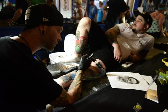 Nick Daugherty, left, takes a look at the drawing he tattooed on Levi Kline during the 2019 INKcarceration music festival.