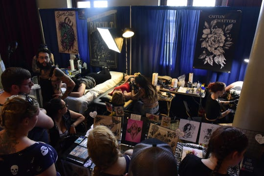 Several people watch as tattoo artists work during the 2019 INKcarceration music festival.