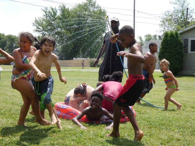 Mount Zion Missionary Baptist Church Pastor Gregory Draper plays with kids Wednesday at the five-week day camp that the church is putting on this summer.