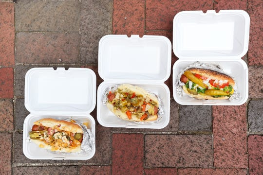 A 'Memphis Belle', from left, The Big Easy', and 'Wrigleyville' style hot dogs by Mac McIntyre of the Hot-n-Heavy Dogs hot dog stand on the corner of Main Street and Union Avenue downtown Memphis on Friday, July 12, 2019.