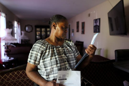 Dorothy Ross looks over paperwork indicating the intent to purchase her house by MLGW, though she says she had no interest in selling the place she had called home for over 40 years. In 2017, she relented and gave up her property to the company. Ross is seen here in her new Frayser home on July 13.
