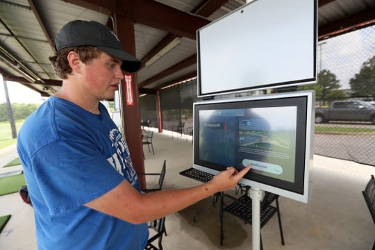 J.P. Johnson, an employee at Vantage Point Golf Center in Cordova, demonstrates the use of a Toptracer range, a system of cameras and digital screens that allow you to see where your ball would land on the world's top courses while examining them for accurate distance measurements on the course Friday, July 12, 2019.