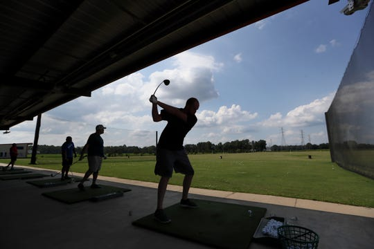 Golfers use a Toptracer range, a system of cameras and digital screens that allow you to see where your ball would land on the world's top courses while examining them for accurate distance measurements at Vantage Point Golf Center in Cordova on Friday, July 12, 2019.