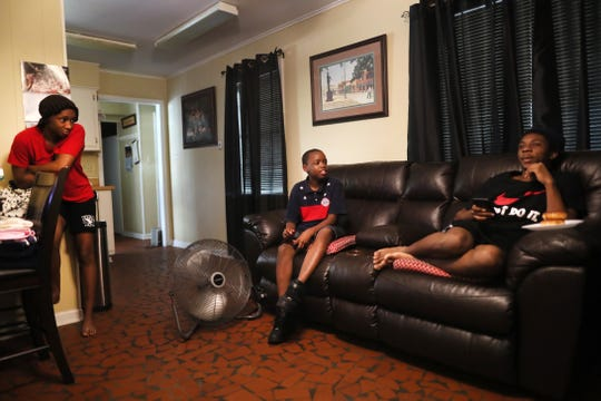 Kendrick Harvey, 19, from right, Angelo Ross, 12, and Andrea Ross, 16, sit in the home they share with their grandmother Dorothy Ross on July 13.