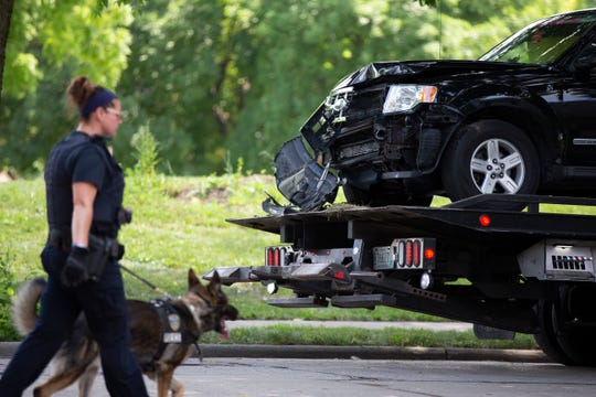 An SUV driven by the suspect in the fatal shooting of a 3-year-old child in a road rage incident Saturday is towed from the scene where it crashed.