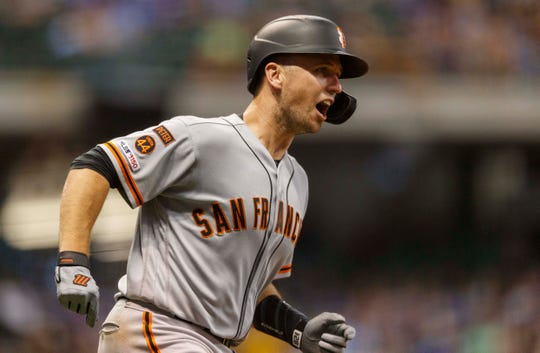 Giants catcher Buster Posey rounds the bases after hitting a grand slam in the 10th inning at Miller Park.