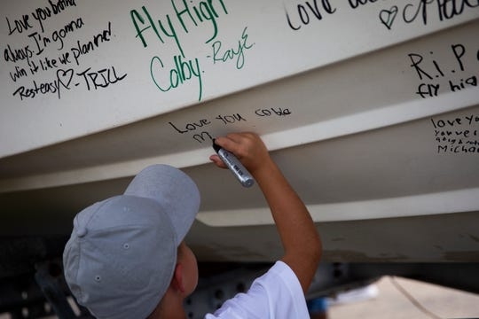 Colton Kersey, 6, writes a message on a boat during a celebration of life for Colby Singletary at the Collier County Fairgrounds on Saturday. Singletary, a star wrestler and football player at Palmetto Ridge High School, died in a car crash on July 6.