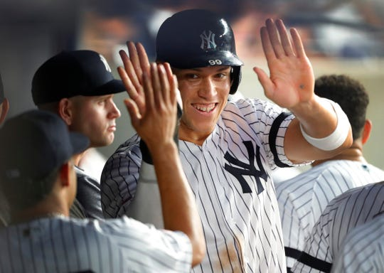 Jul 12, 2019; Bronx, NY, USA;   New York Yankees right fielder Aaron Judge (99) celebrates in the dugout after scoring in the fifth inning against the Toronto Blue Jays at Yankee Stadium.