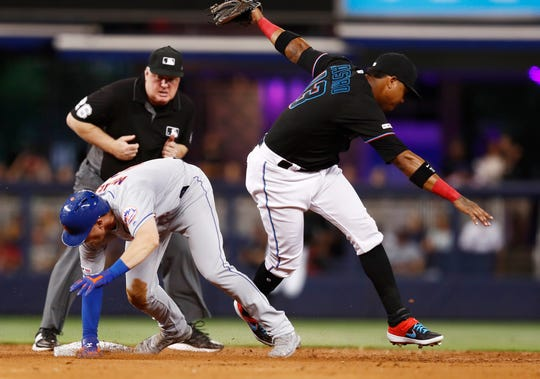 New York Mets' Jeff McNeil (6) slides safely into second base next to Miami Marlins second baseman Starlin Castro (13) during the inning of a baseball game Friday, July 12, 2019, in Miami.