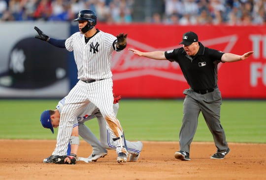 Jul 12, 2019; Bronx, NY, USA;   New York Yankees catcher Gary Sanchez (24) is safe after a late tag by Toronto Blue Jays second baseman Cavan Biggio (8) in the fourth inning at Yankee Stadium.