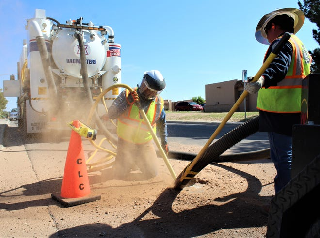 LCU Gas worker Steve Barela pushes dirt out of a hole in the pavement to find gas lines without having to open up the entire street. The dirt is sucked up by the vacuum controlled by LCU Heavy Equipment Operator Mannie Rosales, and then filled back in after the lines are found, inspected, and repaired as needed.