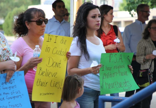 Dora Coronado and Arely Caro hold signs protesting the detention of undocumented immigrants and separation of families.