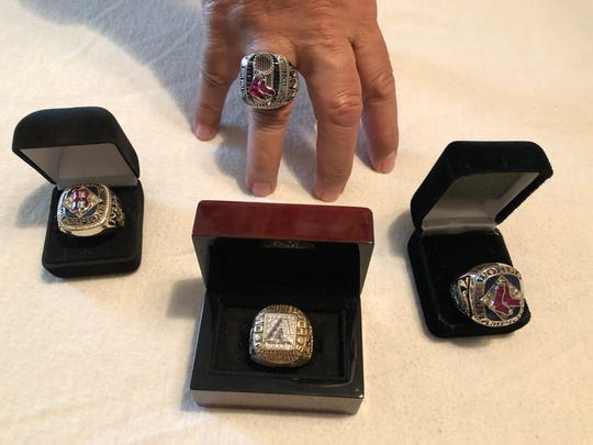 Russell Nua wears the Boston Red Sox 2013 World Series ring. From left, in the boxes are the Boston Red Sox 2004 World Series ring, Arizona Diamondbacks 2001 World Series ring and Boston Red Sox 2007 World Series ring. Not pictured is the Boston Red Sox 2018 World Series ring that Nua was awarded with the team at the beginning of the 2019 MLB season.
