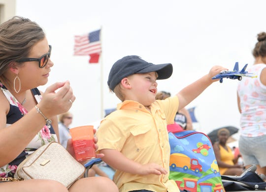 Chelsea Ingram, of Dothan, Alabama, watches as her son Banks, 3, plays with this toy airplane prior to the Blue Angels show over Pensacola Beach on Saturday, July 13, 2019.