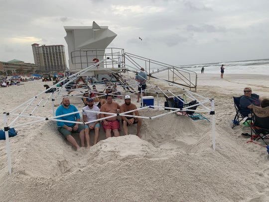 """A crew from Mobile, Alabama, is building a """"tropical storm fortress"""" to protect themselves from the winds and the rain, and to give them a place to retreat if the weather gets bad Saturday, July 13, 2019, at Pensacola Beach ahead of the Blue Angels Air Show."""