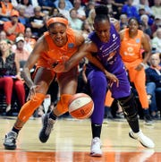Connecticut Sun forward Kristine Anigwe, left, and Phoenix Mercury forward Sancho Lyttle reach for the ball during a WNBA basketball game Friday, July 12, 2019, in Uncasville, Conn.