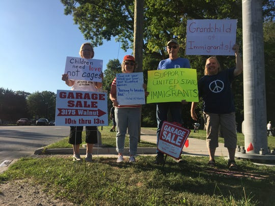 "A few St. Clair County Democrats hold up signs toward the end of a local ""Lights for Liberty"" event Friday night, July 12, 2019, in Port Huron, as other protesters pack it up behind them. Like coordinated events across the country Friday, it aimed to challenge the conditions of facilities and system encountered by migrants along the southern border."