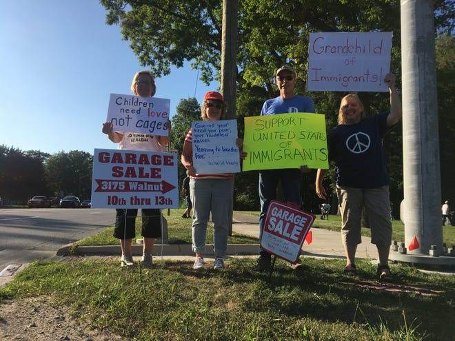 """A few St. Clair County Democrats hold up signs toward the end of a local """"Lights for Liberty"""" event Friday night, July 12, 2019, in Port Huron, as other protesters pack it up behind them. Like coordinated events across the country Friday, it aimed to challenge the conditions of facilities and system encountered by migrants along the southern border."""