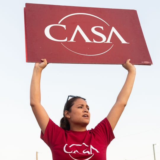 Sara Salazar holds her CASA sign up high during the Lights for Liberty candlelight vigil in front of the York County Prison ICE Detention Center, July 12, 2019.