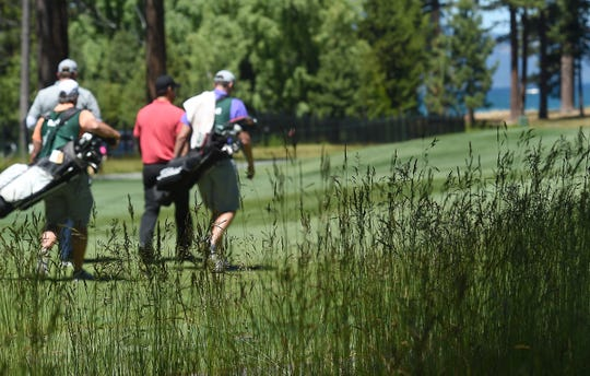 Tony Romo, in pink, walks up the 9th fairway during the 2019 American Century Championship at the Edgewood Tahoe Golf Course on July 13, 2019.