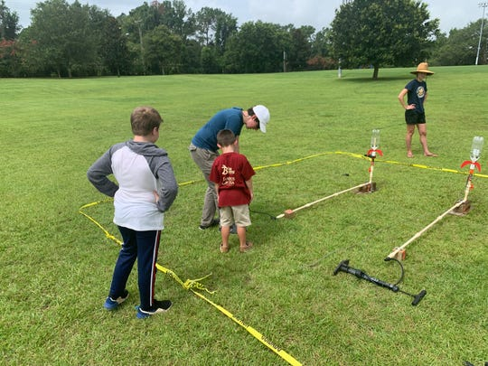 Event organizer Atilla Sulker helps a child launch his bottle rocket at the The Tally Rocket Faire event Saturday at Apalachee Regional Park.