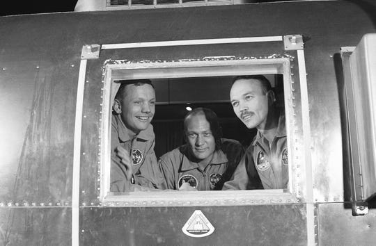 In this July 27, 1969, file photo, Apollo 11 crew members, from left, Neil Armstrong, Buzz Aldrin and Michael Collins sit inside a quarantine van in Houston.