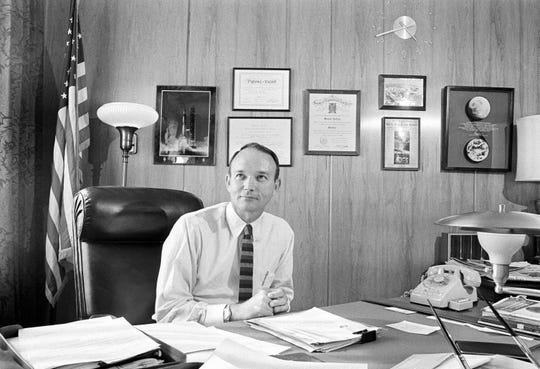"In this June 25, 1970, file photo, Mike Collins, the third man of the Apollo 11 moon landing mission, sits at his State Department desk in Washington. ""Any time one changes jobs and scenes it's a little new and strange,"" said the former astronaut. After six months, he said he felt quite comfortable and trophies on the wall behind him helped him feel at home."