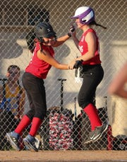 Laurel's Keirsten Passwaters (left) celebrates with runner Ryley McCluskey after they scored on Melea Pusey's drive in the fourth inning of Laurel's 6-2 win to force a Saturday rematch against Camden-Wyoming to decide the Delaware major softball state tournament.