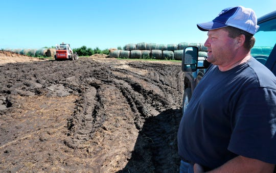 This photo taken July 2, 2019, shows Lannie Mielke talking about the muddy tracks left in the soil by his feeding equipment near a cattle feedlot his farm. Mielke and other area farmers around Aberdeen are having problems with planting and day to day operations due to wet ground caused by spring runoff and rainfall, Mielke said nearly six inches of rain fell on some of his land at the end of June.