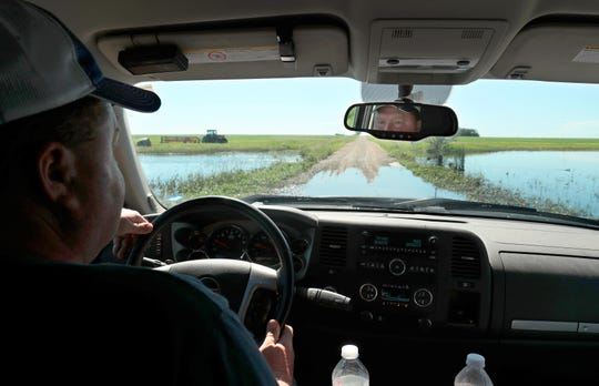 Tis photo taken July 2, 2019, shows Lannie Mielke driving through standing water on the road near his farm in Aberdeen, S.D. Mielke and other area farmers around Aberdeen are having problems with planting and day to day operations due to wet ground caused by spring runoff and rainfall, Mielke said nearly six inches of rain fell on some of his land at the end of June.