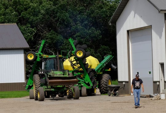In this July 1, 2019, photo, Larry Ness puts spring planting equipment into storage at their farm near Comstock, Minn. The Ness family fears they will be forced to leave the farmstead where the family has lived since 1942.