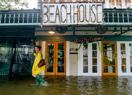 Aimee Cutter,  the owner of Beach House restaurant, walks through water surge from Lake Pontchartrain on Lakeshore Drive in Mandeville, La., ahead of Tropical Storm Barry, Saturday, July 13, 2019.