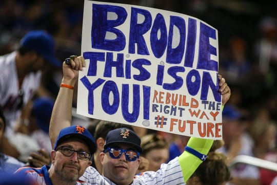 A fan holds up a sign directed at Mets GM Brodie Van Wagenen.