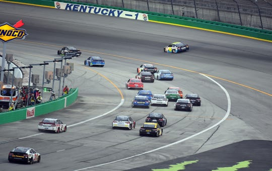 NASCAR Cup Series drivers reenter the track after a pit stop at the end of Stage 1 during the 2018 Quaker State 400 at Kentucky Speedway.