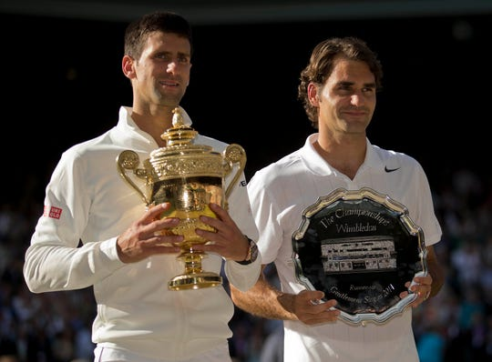 Novak Djokovic and Roger Federer with their trophies after the men's singles 2014 Wimbledon Championships at the All England Lawn and Tennis Club.