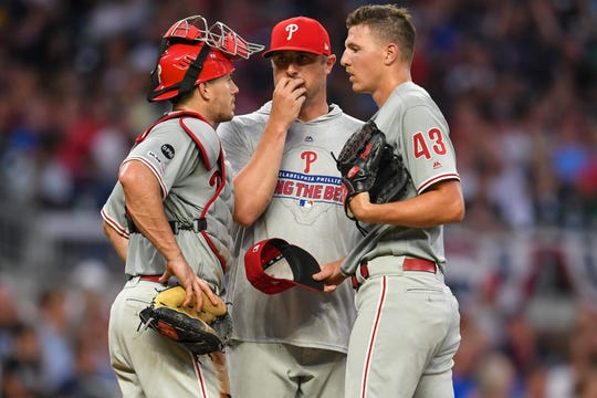 Philadelphia Phillies catcher J.T. Realmuto, left, pitching coach Chris Young, center, and pitcher Nick Pivetta (43) meet on the pitchers mound during a July 3 game against the Atlanta Braves.