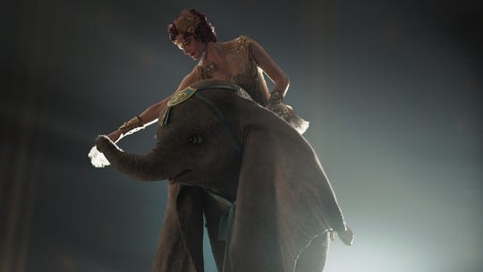 "The aerialist Colette Marchant (Eva Green) prepares to take flight with the title elephant of Tim Burton's ""Dumbo."""
