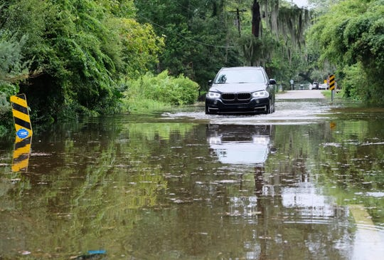 A car drives through a flooded road near Lake Pontchartrain as Tropical Storm Barry approaches in Mandeville, La. on July 2019. Tropical Storm Barry is predicted to make landfall on the Louisiana coast soon as a Category 1 hurricane.