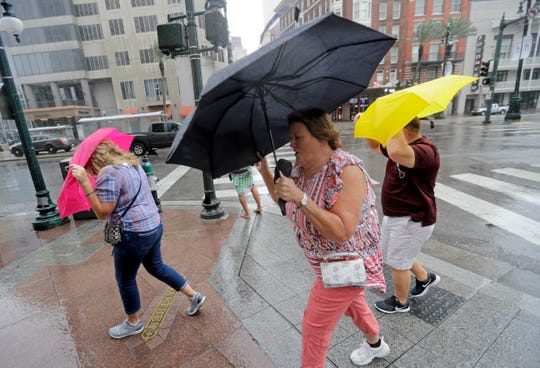 Martha Young, center, Patricia Plishka, left, and her husband Glen, right, battle the wind and rain from Hurricane Barry as it nears landfall Saturday, July 13, 2019, in New Orleans.