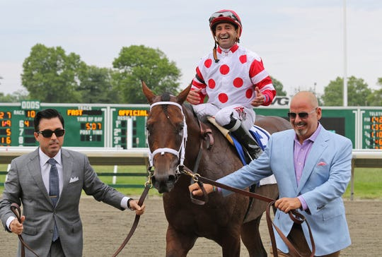 Red Oak Stable owner Steve Brunetti (R) and racing manager Rick Sacco (L) guide King for a Day and Jockey Joe Bravo into the winner's circle after upsetting  Maximum Security and jockey Luis Saez to win the $150,000 TVG.com Pegasus Stakes at Monmouth Park in Oceanport on Sunday June 16, 2019.