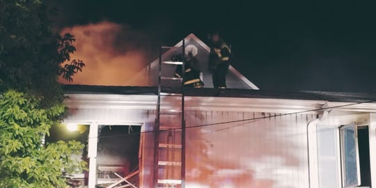 Highlands firefighters work on extinguishing a blaze early Sunday morning at a Fourth Street home.