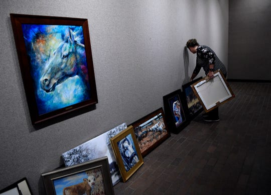 """Shalon Wilson, the executive director for the Breckenridge Fine Arts Center, arranges paintings as she decides how to hang them Thursday. On the wall hangs Iwona Jankowski's """"Twilight Shadow - Mottled Horses""""."""